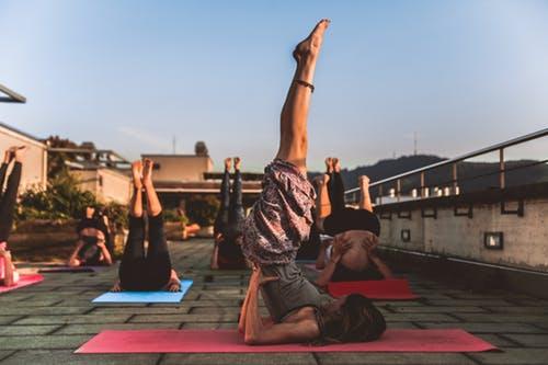 cours collectif de yoga en extérieur posture sarvangasana