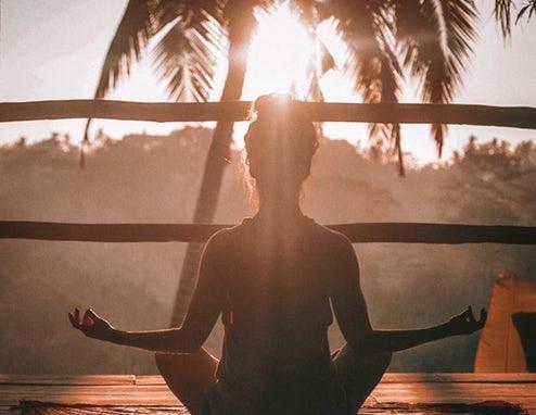 femme de dos en méditation au crépuscule