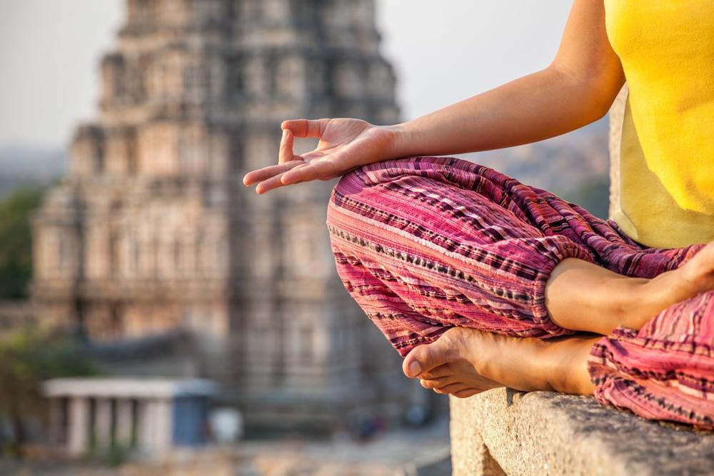 une femme en demi-lotus pratique la méditation en inde