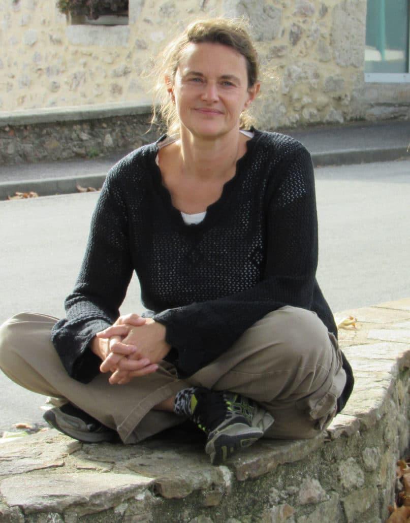 anne gauby professeur de yoga en tailleur sur un muret