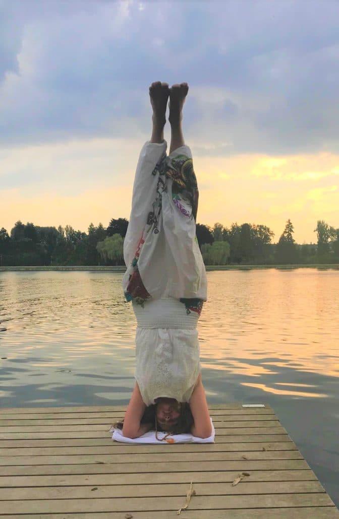anne gauby professeur de yoga en posture sur la tête au bord d'un lac