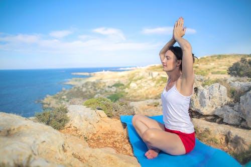 femme en posture de yoga sur les rochers en bord de mer